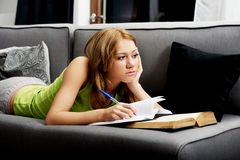 Young woman learning to exam on a sofa. Young teenage woman learning to exam on a sofa Stock Images