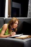 Young woman learning to exam on a sofa. Young teenage woman learning to exam on a sofa Stock Photos