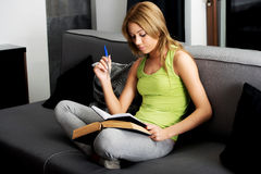 Young woman learning to exam on a sofa. Royalty Free Stock Photo