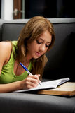 Young woman learning to exam on a sofa. Stock Images