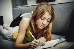 Young woman learning to exam on a sofa. Royalty Free Stock Image