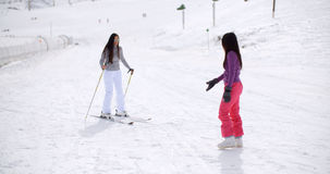 Young woman learning to ski from a friend Stock Image
