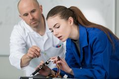 Young woman learning to solder wire. Young women learning to solder wire electronic royalty free stock images