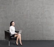 Young woman in leather armchair near concrete wall Stock Images