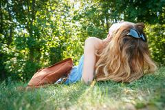 Young woman with a leather backpack on a summer forest grass. Young woman with a leather backpack lying on a grass in a summer park Stock Photos