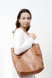 Young woman with leather bag Stock Photography