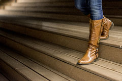 Young woman in leather boots. Standing on wooden stairs at night Royalty Free Stock Images