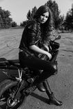 Young woman in leather clothes near a motorcycle. Black and white photo royalty free stock photography