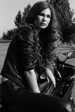 Young woman in leather clothes near a motorcycle. Black and white photo stock photography