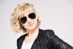 Young woman in leather jacket. Young blonde woman wearing black leather jacket and sunglasses Stock Photo
