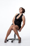 Young woman in leather jacket, miniskirt, high heels, with excep. Tional haircut sitting on a swivel chair Royalty Free Stock Photos