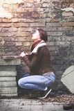 Woman with leather jacket praying in front of an old wall royalty free stock images