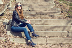 Young woman in leather jacket resting on stairs Royalty Free Stock Photos