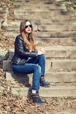 Young woman in leather jacket resting on stairs Stock Images