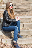 Young woman in leather jacket resting on stairs Stock Photo
