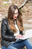 Young woman in leather jacket using laptop. Young woman in glasses and leather jacket using laptop on the stairs. Pretty caucasian girl sitting on stairs working Royalty Free Stock Photos