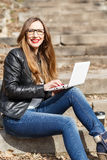 Young woman in leather jacket using laptop. Young woman in glasses and leather jacket using laptop on the stairs. Pretty caucasian girl sitting on stairs working Royalty Free Stock Photo