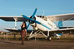 Young woman in leather skirt walking near the airplane outdoors on the airport runway stock image