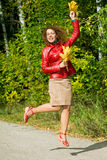 Young woman with leaves in hands in jump in autumn Stock Images
