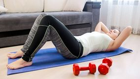 Young woman in leggings lying on fitness mat and doing sit-ups. Young woman in leggings lying on mat and doing sit-ups Stock Photo