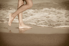 Young woman legs on the beach at sunset. Beautiful young woman legs on the beach at sunset, sepia toned image Stock Image