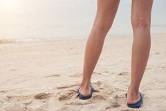 Young woman legs in flipflop sandals on sea beach.  royalty free stock photography