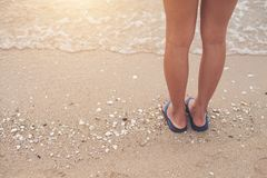 Young woman legs in flipflop sandals on sea beach. Young man legs in sandals on sea beach stock photo