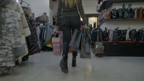 Young woman legs in heels walking in a clothing store mall while the hands are full of shopping bags -. Young woman legs in heels walking in a clothing store stock footage