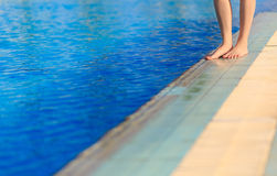 Young woman legs standing on border front of swimming pool Stock Photo