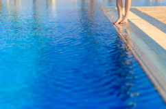 Young woman legs standing on border front of swimming pool Royalty Free Stock Photo
