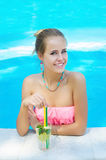 Young woman with lemonade in the pool Stock Image