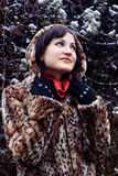 Young woman in leopard fur coat looking up. Young woman in leopard fur coat and hood wondering Royalty Free Stock Photos