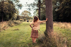 Young woman lesaning against a tree in the forest Royalty Free Stock Photo