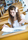 Young woman in library. Beautiful young woman in library with book Stock Images