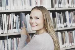 Young woman in library. Beautiful young woman looking for books in a library Royalty Free Stock Photos