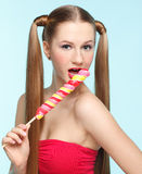 Young woman licking lollipop Stock Images