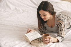 Young woman lie on bed with a book rest Stock Image