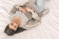 Young woman lie on bed with a book rest Stock Photos