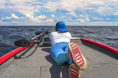 Young woman lie on fishing boat with fish finder, echolot, sonar aboard. Young woman lie on fishing boat with fish finder, echolot, sonar and structure scaner royalty free stock image