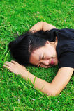 Young woman lie on grass. Young woman lie down on grass and smile Stock Image
