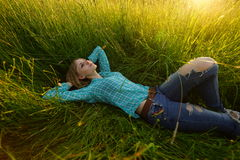 Young woman lie in the high grass. Pretty young woman lie in the high grass on the meadow Stock Images
