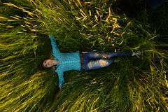 Young woman lie in the high grass. Pretty young woman lie in the high grass on the meadow Royalty Free Stock Image