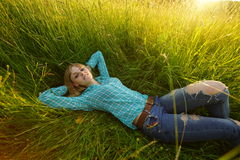 Young woman lie in the high grass. Pretty young woman lie in the high grass on the meadow Royalty Free Stock Images