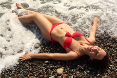 Young woman lies ashore in waves Royalty Free Stock Image