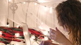 Young woman lies on a bed with a laptop on a garland background, video chat, make an online purchase. Young woman lies on a bed with a laptop on a garland stock footage