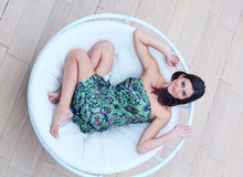 Young woman lies in the circle chaise-longue Stock Photography
