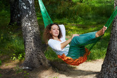Young woman lies with dreamy view in hammock. Suspended between two thick birches royalty free stock image