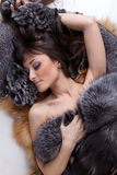 Young woman lies on furs. Royalty Free Stock Photos