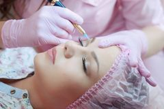 A young woman lies and gets a make-up of her eyebrows in a beauty salon. The use of permanent makeup on the eyebrows. The master w. Orks with the eyebrows. Semi Royalty Free Stock Photography