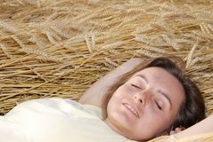Young woman lies in golden grain Royalty Free Stock Photos